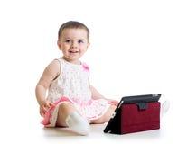 Menina da criança que joga com uma tabuleta digital Imagem de Stock