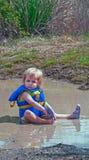 Menina da criança que joga na poça de lama Fotos de Stock