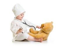 Menina da criança que joga o doutor com urso de peluche Fotos de Stock