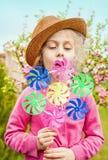 Menina da criança que joga o moinho de vento no jardim de florescência Imagens de Stock