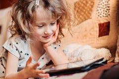 Menina da criança que joga a tabuleta em casa Foto de Stock
