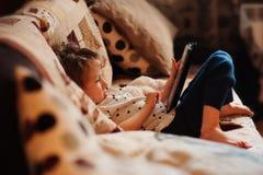 Menina da criança que joga a tabuleta em casa Fotografia de Stock