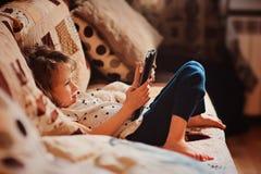 Menina da criança que joga a tabuleta em casa Imagem de Stock