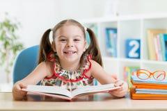 Menina da criança que lê um livro imagem de stock