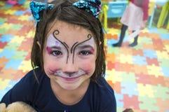 Menina da criança que levanta a cara pintada durante na sala de jogos das crianças fotos de stock