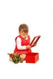 Menina da criança que olha no presente do Natal Fotografia de Stock Royalty Free
