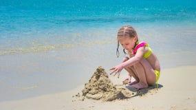 Menina da criança que palying com a areia na praia fotografia de stock