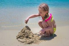 Menina da criança que palying com a areia na praia imagem de stock royalty free