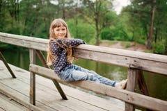 Menina da criança que senta-se em uma ponte de madeira perto da água Imagens de Stock Royalty Free