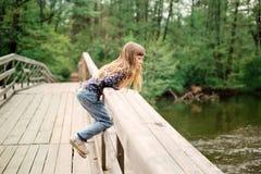 Menina da criança que senta-se em uma ponte de madeira perto da água no rive Foto de Stock