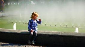 Menina da criança que senta-se perto de uma fonte em um parque da cidade video estoque