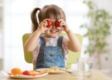 Menina da criança que tem o divertimento com os vegetais do alimento na sala do berçário imagens de stock