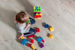 Menina da criança que tem o divertimento e a construção de blocos plásticos brilhantes da construção Imagens de Stock