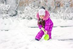 Menina da criança que trabalha com pá a neve na maneira home da movimentação foto de stock royalty free