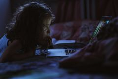 Menina da criança que usa o portátil e olhando filmes na noite apenas em sua sala imagem de stock royalty free