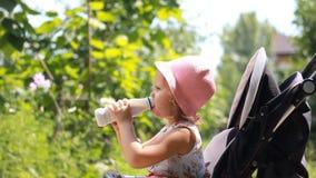 A menina da criança senta-se em um carrinho de criança e bebe-se uma bebida de leite de uma garrafa ou de um kefir video estoque