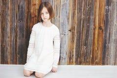 Menina da criança sobre a parede de madeira Imagens de Stock Royalty Free