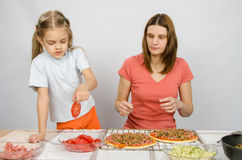 A menina da criança de seis anos toma a placa de tomates do corte para a pizza sob a supervisão do mum Imagens de Stock