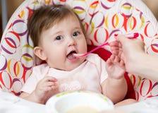 Menina da criança do bebê que come o alimento com ajuda da mãe Fotografia de Stock