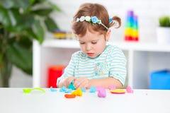 A menina da criança esculpe da argila Fotografia de Stock