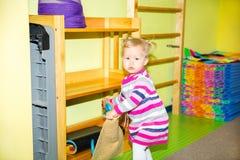 Menina da criança pequena que joga no jardim de infância na classe do pré-escolar de Montessori Criança adorável na sala do berçá Fotografia de Stock