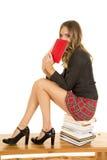 A menina da escola atrás do livro senta-se na pilha imagens de stock royalty free