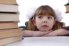 A menina da escola está olhando o montão dos livros. Imagens de Stock Royalty Free