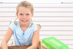 Menina da escola na mesa de encontro à linha fundo da escrita. Fotografia de Stock Royalty Free
