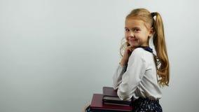 A menina da escola no uniforme senta cotovelos em livros e sorriso na câmera Vista lateral vídeos de arquivo