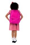 Menina da escola primária que enfrenta a parede Foto de Stock Royalty Free