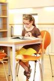 Menina da escola que estuda na biblioteca Imagem de Stock
