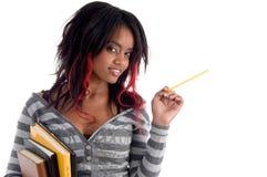 Menina da escola que levanta com lápis e livros Imagens de Stock