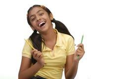 Menina da escola que prende uma cor de dois lápis Imagens de Stock Royalty Free
