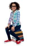 Menina da escola que senta-se na pilha de livros Imagem de Stock Royalty Free