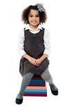 Menina da escola que senta-se na pilha dos livros Fotografia de Stock Royalty Free