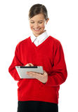 Menina da escola que usa o dispositivo de almofada novo do toque Imagens de Stock Royalty Free