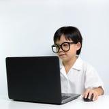 Menina da escola que usa o portátil Foto de Stock