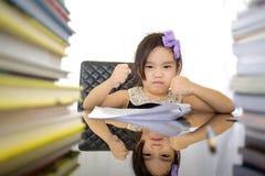Menina da escola que veste uns trabalhos de casa fazendo totais fotografia de stock royalty free
