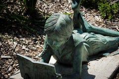Menina da estátua que lê um livro Fotografia de Stock