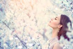 Menina da forma da mola em árvores de florescência Fotografia de Stock Royalty Free