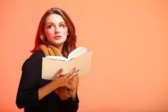 Menina da forma do outono com olho-chicotes da laranja do livro Imagem de Stock