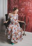 Menina da forma na cadeira A benevolência e a elegância das mulheres Fotos de Stock Royalty Free