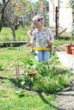A menina da forma nos óculos de sol aprecia balançar no dia ensolarado Criança pequena no balanço na jarda do verão Criança da be imagem de stock royalty free