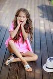 Menina da forma que veste uma camisa, um chapéu e uns óculos de sol quadriculados cor-de-rosa na cidade fotos de stock royalty free