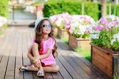 Menina da forma que veste uma camisa, um chapéu e uns óculos de sol quadriculados cor-de-rosa na cidade imagem de stock royalty free
