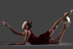 Menina da ginasta que faz o exercício do backbend com bola fotografia de stock