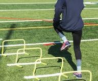 Menina da High School que executa brocas atléticas no relvado fotografia de stock royalty free