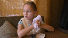 Menina da jovem mulher que senta-se na tabela no café e que limpa suas mãos com uma toalha molhada e que prepara-se para comer o  filme