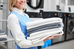 Menina da lavanderia do trabalhador que guarda toalhas frescas em seus mãos e sorrisos Imagens de Stock