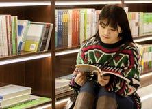 Menina da leitura da livraria Foto de Stock